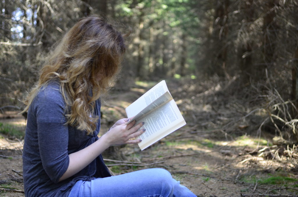 Dziewczyna czytająca książkę w lesie, rozpuszczone jasne włosy, szary sweter, jeansy, szare kolory lasy, skrawki słońca.