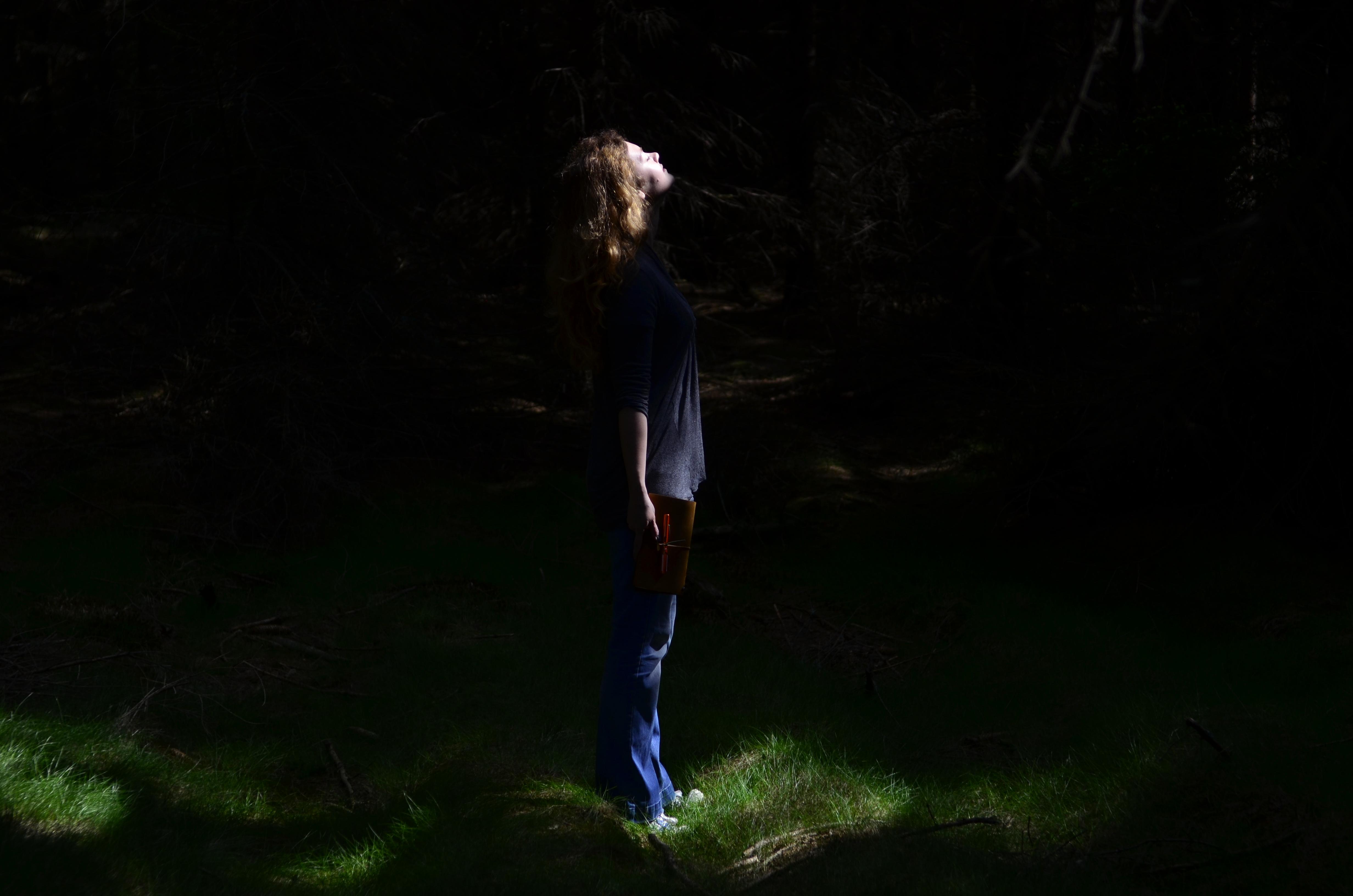 Dziewczyna w środku ciemnego lasu oświetlona promieniami słońca.
