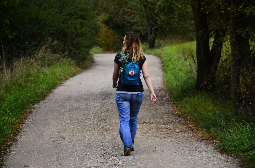 Dziewczyna idąca drogą, odwrócona do obiektywy tyłem, na plecach plecak kanken z wetkniętymi w niego kwiatami. Wokół zieleń, panuje lato, droga wiejska.