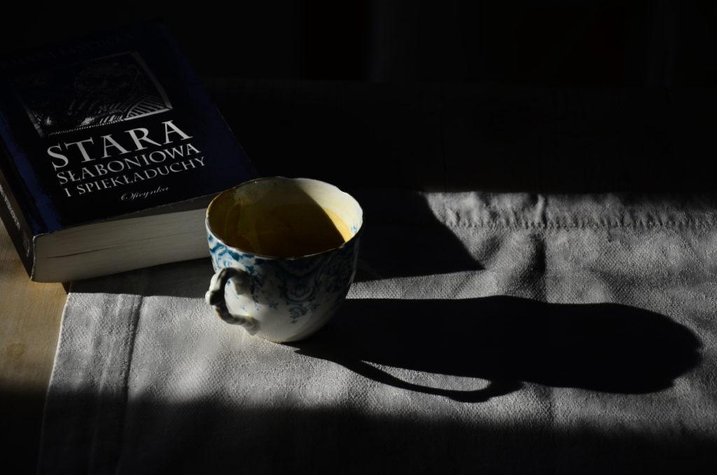 Książka leżąca na stole na białym obrusie w świetle słońca, obok filiżanka