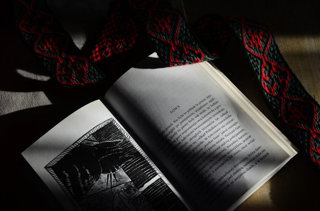 Otwarta książka leżąca na stole w świetle słońca obok czerwono-zielona krajka.