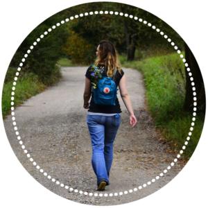 dziewczyna z plecakiem idąca lesną drogą