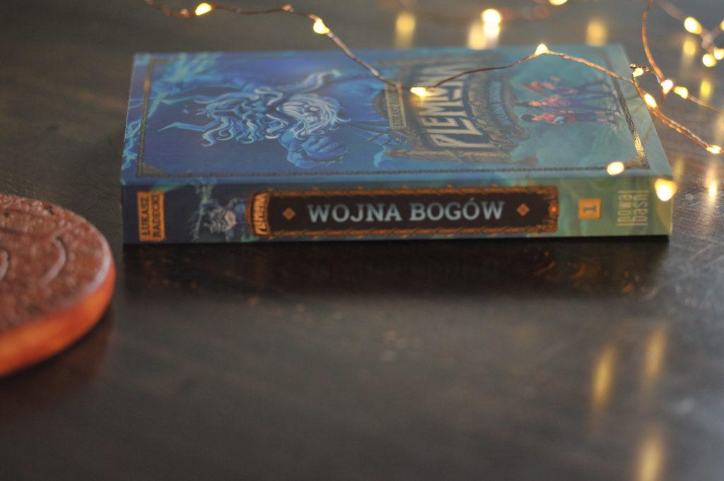 """Książka """"Plemiona. Wojna bogów"""" leżąca na stole, w tle światełka."""