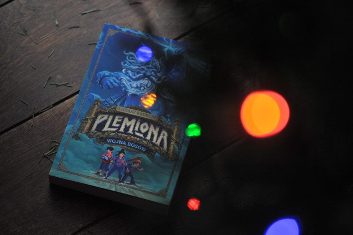 Książka plemiona leżąca na drewnianej podłodze, otoczona kolorowymi światełkami.
