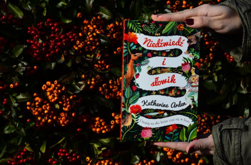 """Książka """"Niedźwiedź i słowik"""" trzymana w dłoniach na tle krzewi pełnego pomarańczowych jagód."""