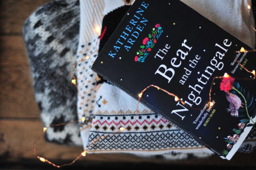 """Angielska książka """"Niedźwiedź i słoik"""" leżąca na stosie swetrów."""