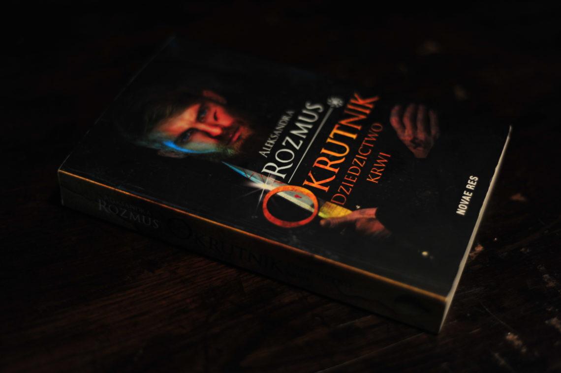 """Książka """"Okrutnik"""" leżąca w ciemności na drewnianym stole."""