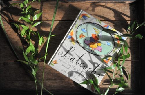 książka leżąca na drewnianej tacy w promieniach słońca i zielonych roślinach