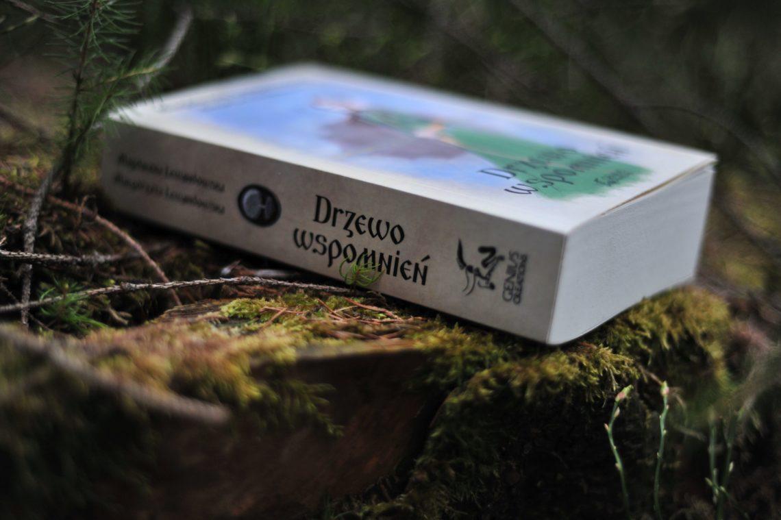 """Książka """"Drzewo wspomnień"""" leżące na pniu porośniętym mchem."""