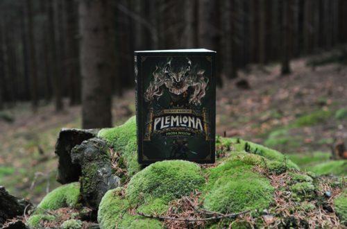 """Książka """"Próba bogów. Plemiona"""" w lesie, na mchu."""