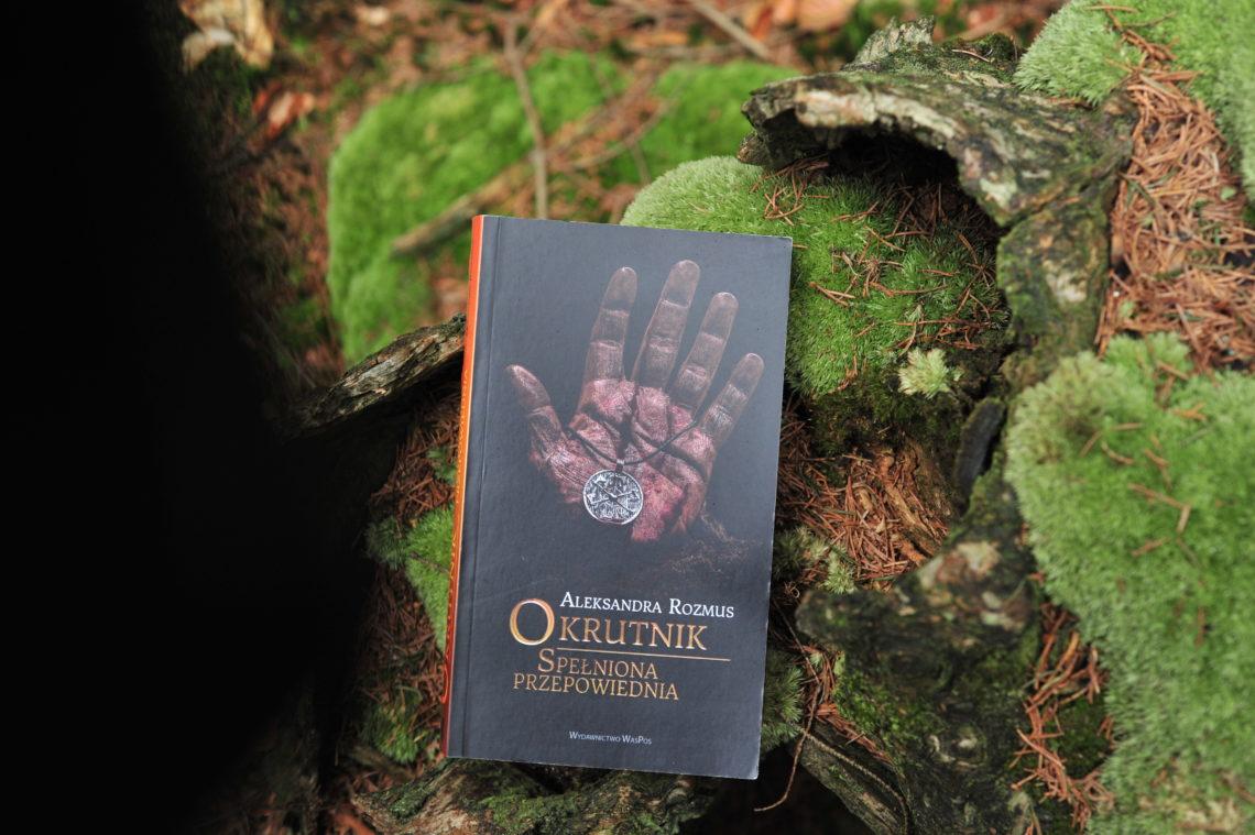 """Książka """"Okrutnik"""" na ściółce leśnej."""