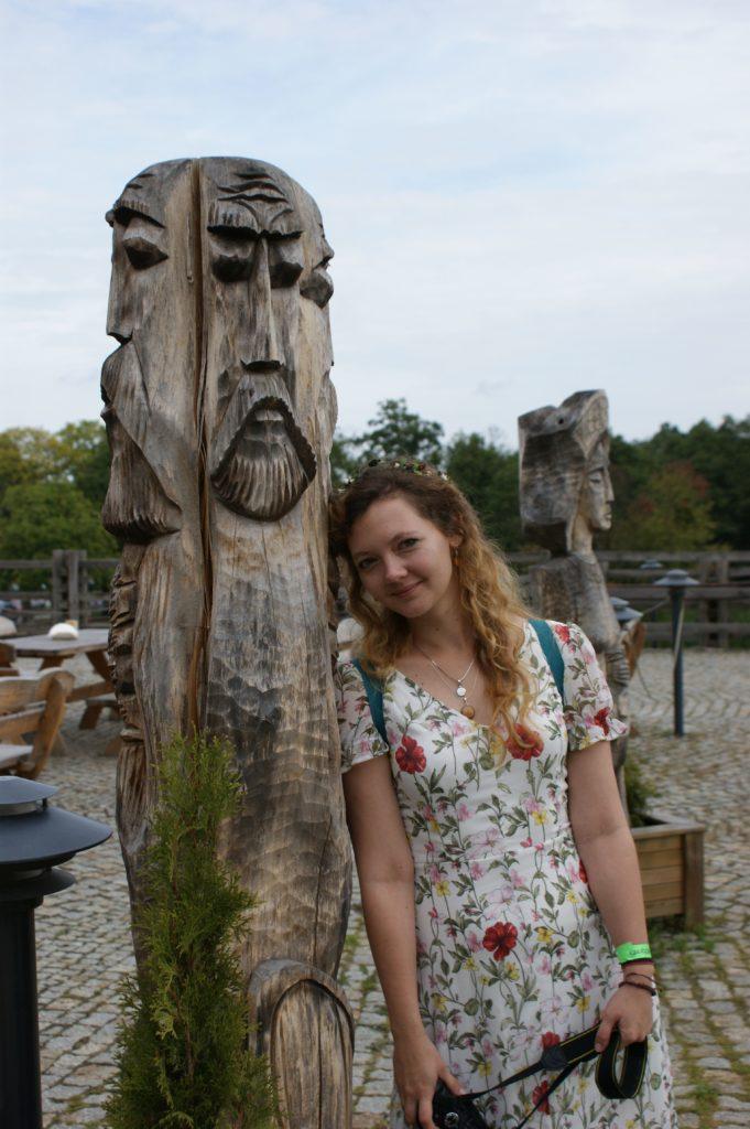 Autorka bloga w kwiecistej sukience przytulona ramieniem do posągu Świętowita