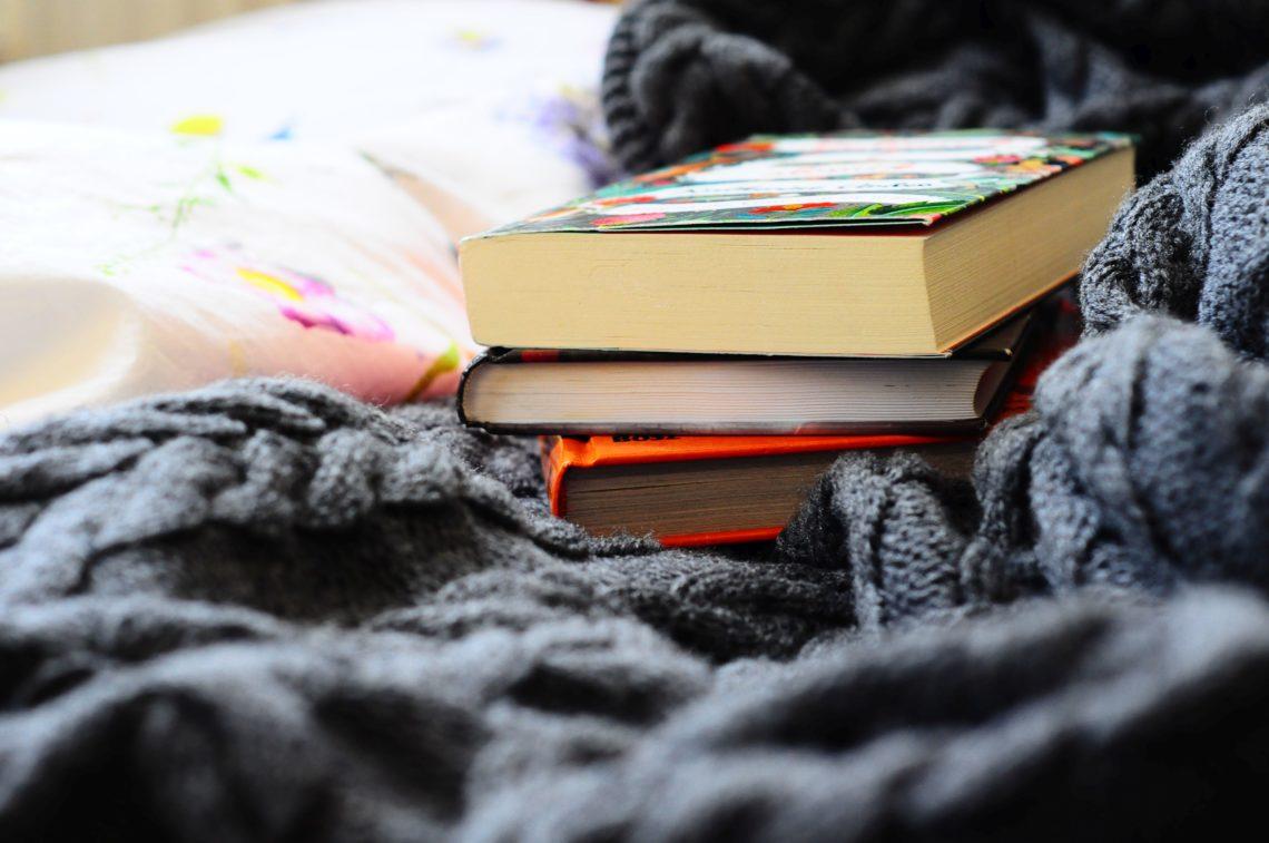 Stos książek leżących na łóżku