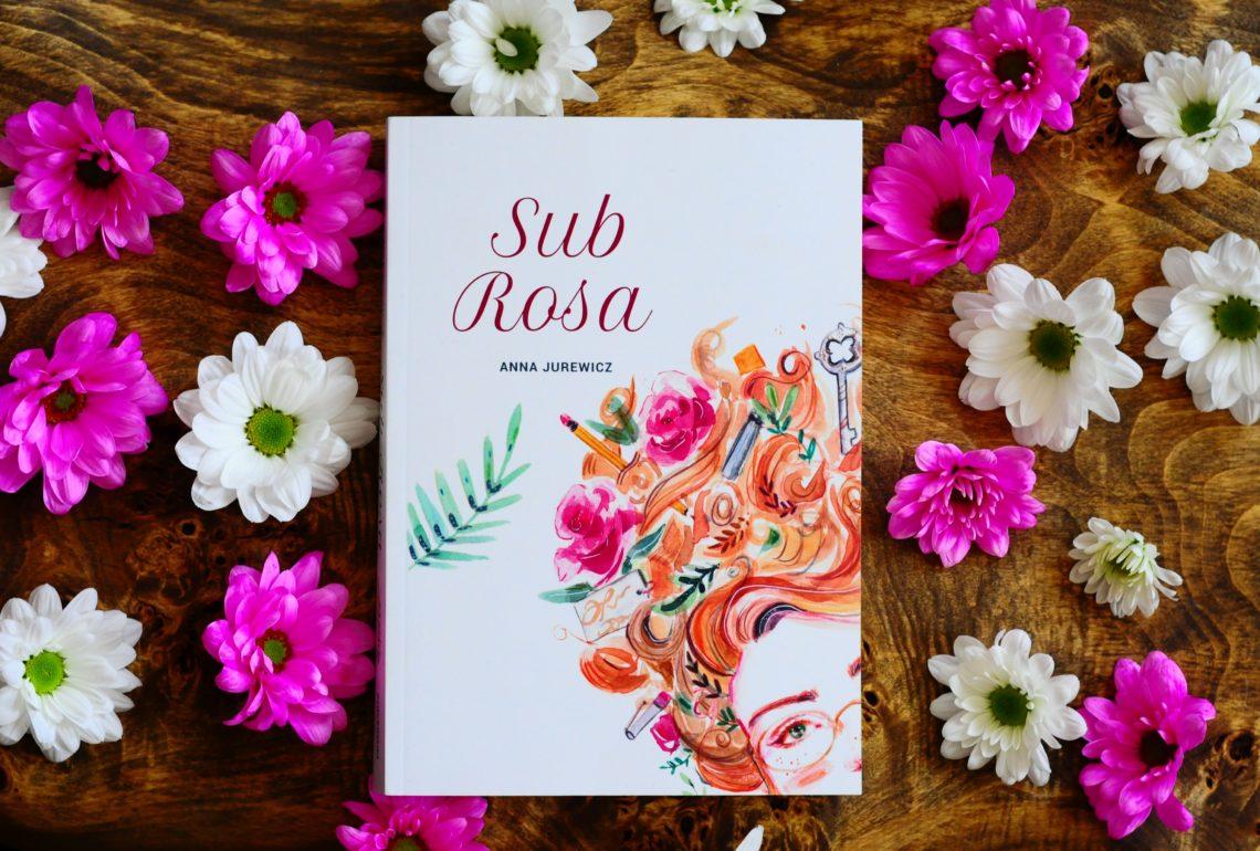 Na drewnianej tacy książka wśród kwiatów białych i różowych.
